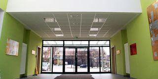 Grün gestrichener Eingangsbereich mit breiter Glastür und neuer Deckenkonstruktion